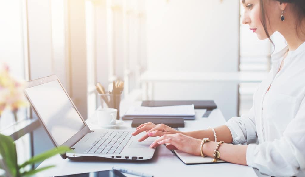 woman writing a blog on a laptop