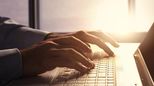 man writing a blog using a laptop keyboard