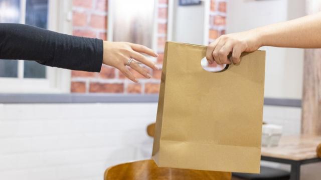 restaurant employee handing food bag to customer